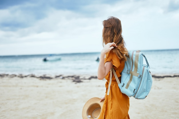 Woman with a blue backpack in a yellow dress and hat walks along the ocean along the sand with palm trees