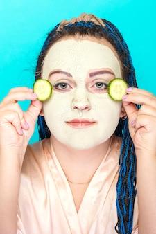 녹색 점토로 만든 냉동 마스크에 파란색 머리띠 얼굴을 가진 여자