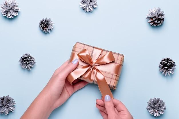 파란색 매니큐어가 공예 종이 선물 상자를 들고 있거나 파란색 배경에 은색 솔방울과 색종이 조각으로 포장된 선물을 가진 여자. 크리스마스 선물 또는 쇼핑 개념입니다. 평면도