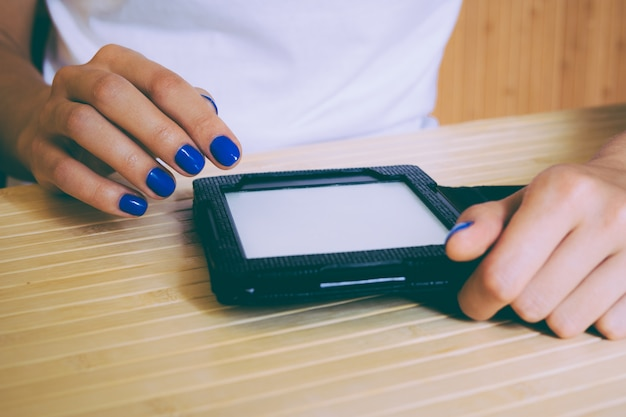 Woman with blue manicure reading an e-book at a wooden table