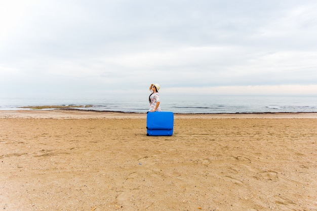 Woman with blue suitcase on the beach. funny picture, joke and humor concept.