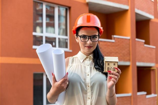建物の背景に青写真と家のモデルを持つ女性