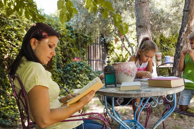 Donna con libro e bambini in giardino