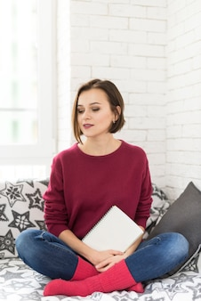 Woman with book in hand waiting on sofa
