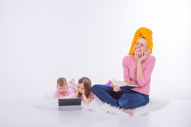 Женщина с книгой в руках разговаривает по телефону. дети смотрят мультфильм на планшете. мама вымыла волосы. полотенце на голову. хобби и отдых с гаджетами.