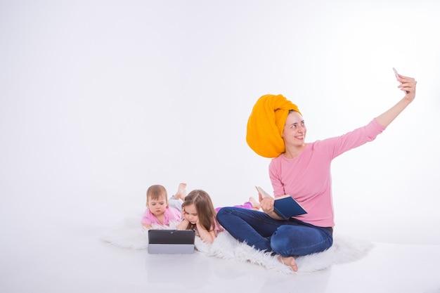 彼女の手で本を持つ女性は電話で話しています。子供たちはタブレットで漫画を見ます。ママは髪を洗った。頭にタオル。趣味とガジェットでのレクリエーション。