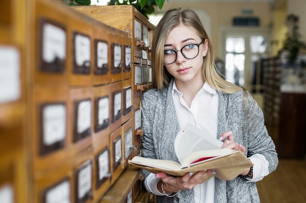 Woman with book leaning on catalog and looking away