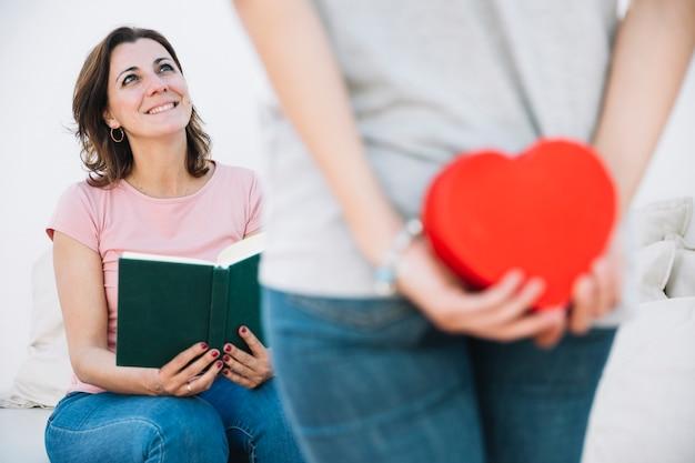 Женщина с книгой, глядя на женщину, делая сюрприз