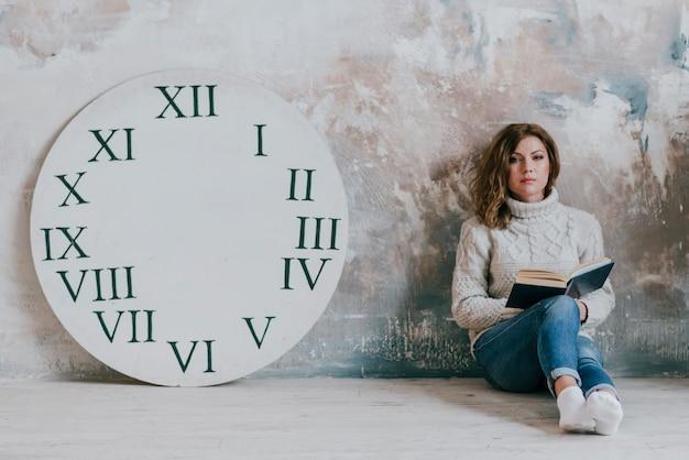 時計のディスクの近くの本を持つ女性