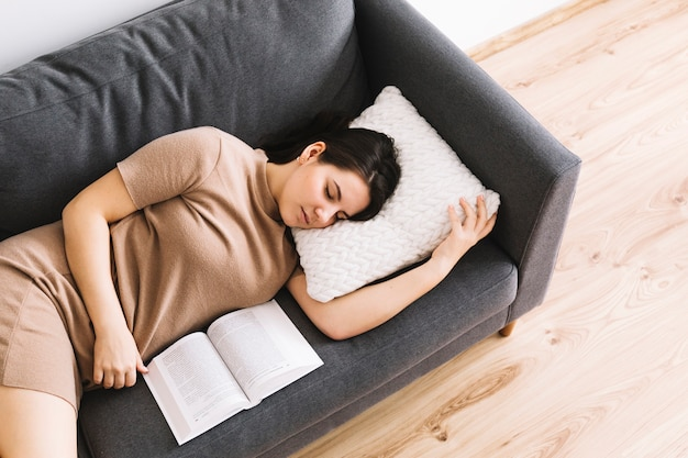 Woman with book sleeping on sofa