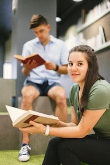 Женщина с книгой, улыбаясь на камеру