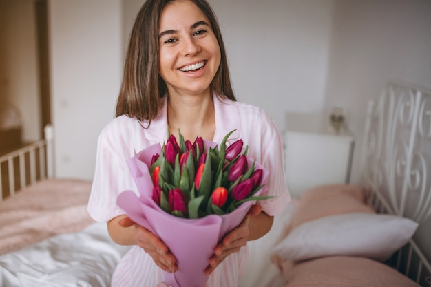 Woman with bouquet of flowers in bedroom