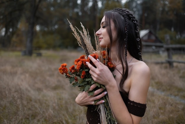 Woman with a bouquet of flowers in a field she holds them near her chest enjoying their scent