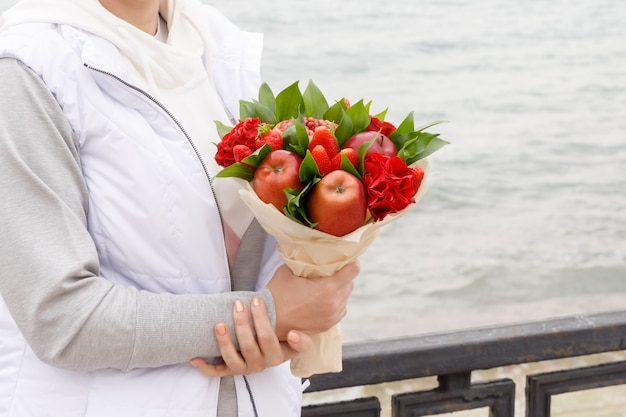 Woman with a bouquet of flowers and fruits stands on the embankment in autumn