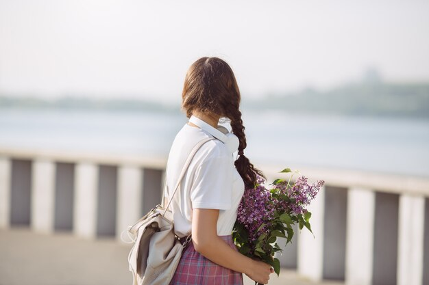 Woman with bouquet of flowers outdoors in the city street