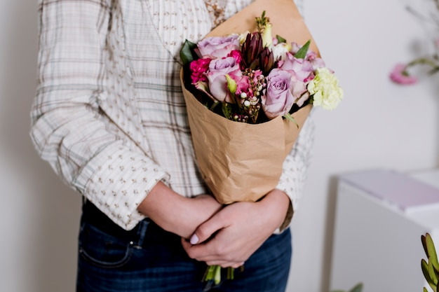 Woman with bouquet of flowers in shop