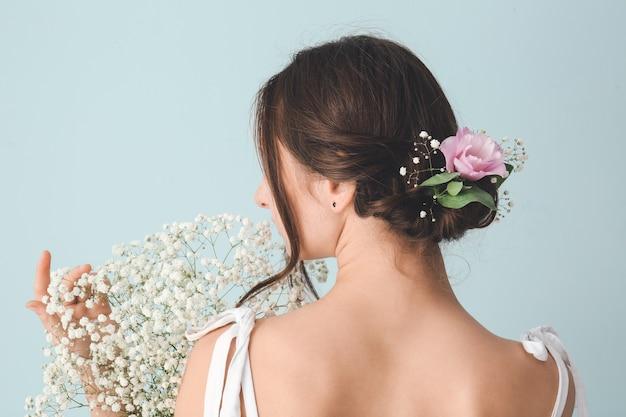 色の背景に美しい花の花束を持つ女性