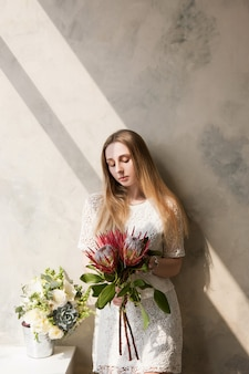 壁の背景に大きな珍しい花の花束を持つ女性。美しい少女の贈り物、花束の配達、花の店のコンセプト