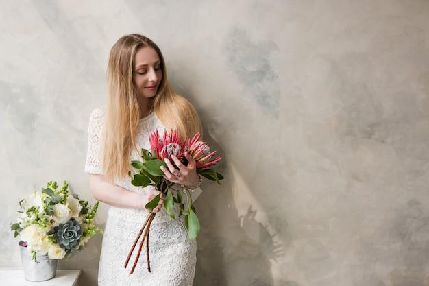 壁の背景にプロテア王の花の花束を持つ女性。美しい少女の贈り物、花束の配達、花の店のコンセプト