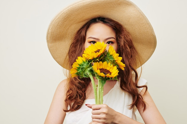 ひまわりの花束を持つ女性