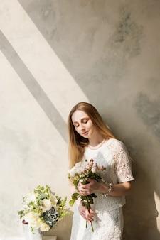 壁の背景に花束を持つ女性。贈り物としての美しい花、花束の配達、花の店のコンセプト
