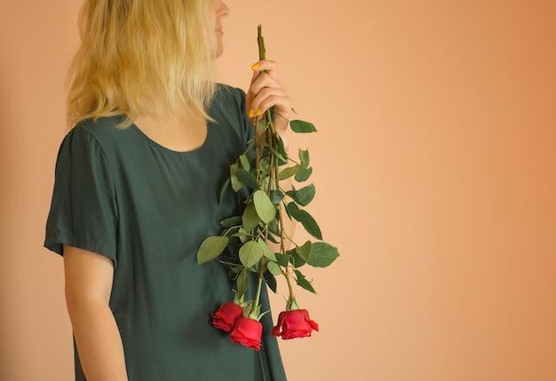 ベージュの背景の上の花束を持つ女性。赤いバラのドレスを着た陽気な少女の肖像画