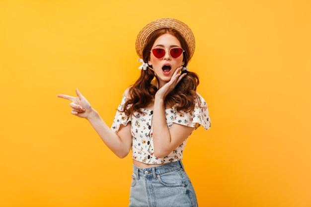 Donna con fiocchi sui capelli e cappello da portare sembra stupita dalla telecamera. donna in occhiali da sole rossi e gonna di jeans punta il dito su sfondo isolato.