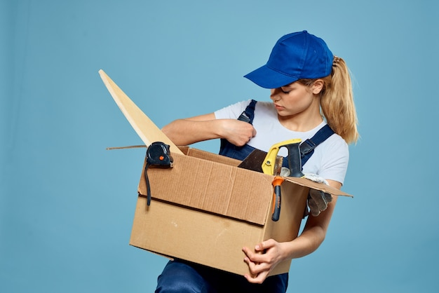 Woman with box in hands delivery service professionals blue