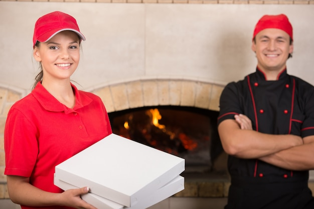 Woman with boxes of pizza in red uniform and chef in black.