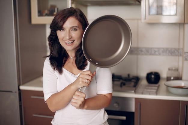 La donna con le parentesi graffe guarda la telecamera e sorride. la signora sta preparando il cibo.