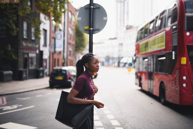 Woman with braids crossing a street in downtown london