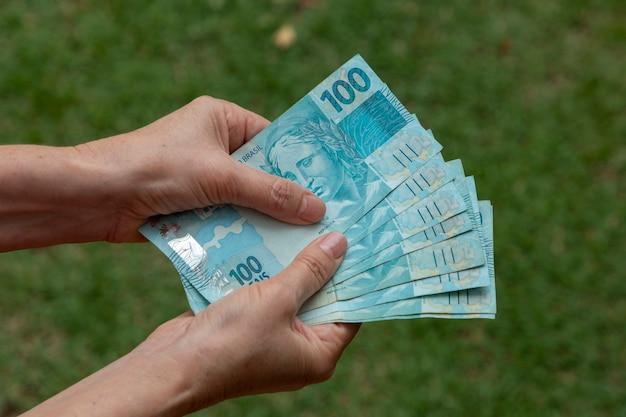 彼女の手にブラジルのお金を持つ女性