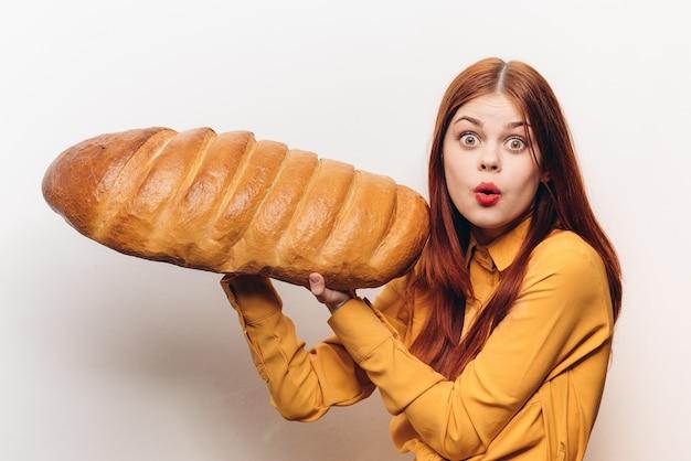 パン、大きな焼きたてのパンを持つ女性