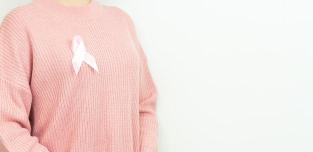 白い背景の上の乳がん啓発リボンを持つ女性。コピースペース