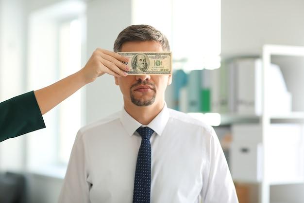 ビジネスマンの目を覆っている賄賂を持つ女性。腐敗の概念