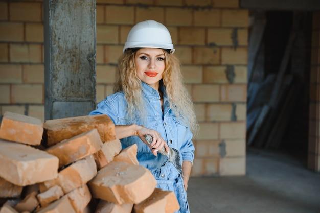 Женщина с кирпичом в концепции строительства