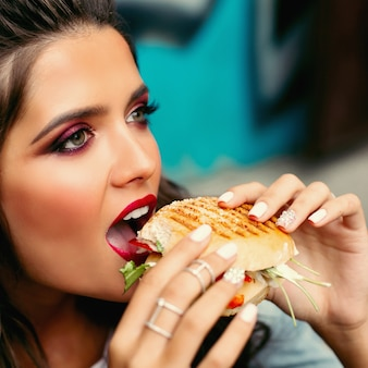 Woman with bright make-up taking a bite of burger.
