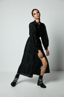 Женщина с ярким макияжем черное платье мода в сапогах.