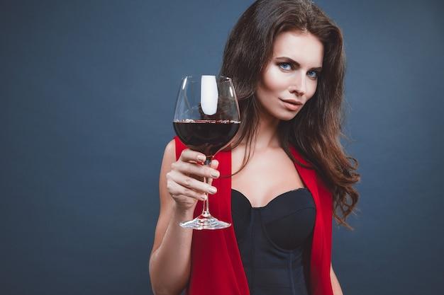 밝은 메이크업을 가진 여자, 어두운 배경 위에 포도 나무의 유리와 함께 포즈를 취하는 빨간 드레스를 입고 헤어 스타일을 분리합니다.