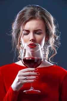 Woman with bright makeup hairstyle wearing red dress posing with glass of vine over dark space isolate
