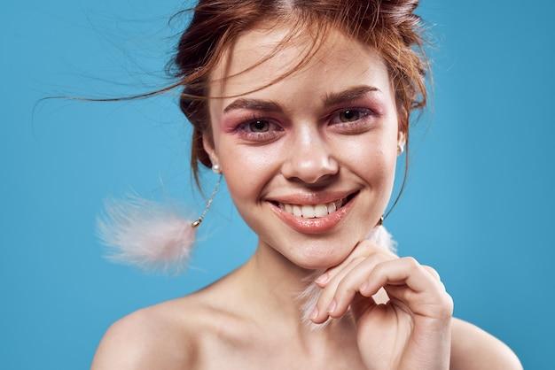 顔の裸の肩の豪華な青い背景に明るい化粧をした女性。