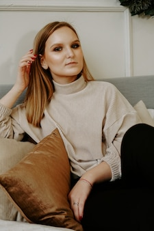 Woman with bright makeup and strict facial features dressed in beige sweater sitting on bed