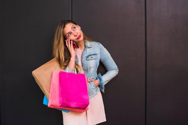 Женщина с яркими сумками разговаривает по телефону