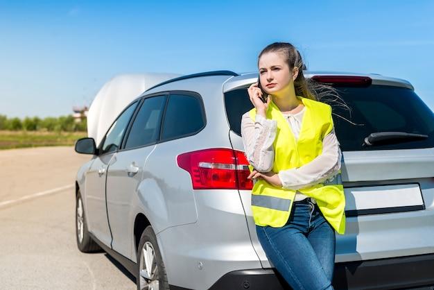 도움을 요청하는 깨진 된 자동차와 여자