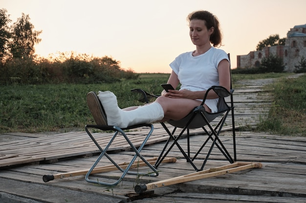 Woman with broken in cast is sitting on chair in nature and is chanting by phone