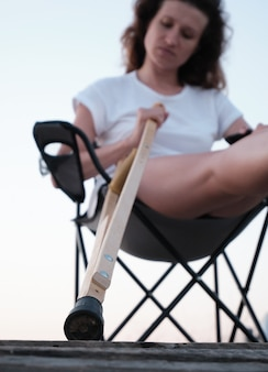 Woman with broken in cast is sitting on chair in nature leg injury rehabilitation after a fracture