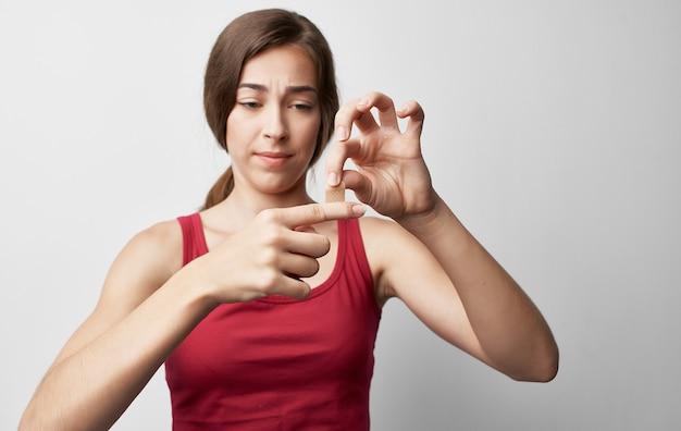 Женщина со сломанным пальцем в красных проблемах со здоровьем травмы футболки.
