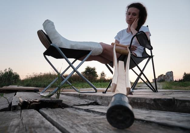 ギプスで壊れた女性は、骨折後の自然の脚の怪我のリハビリテーションで椅子に座っています