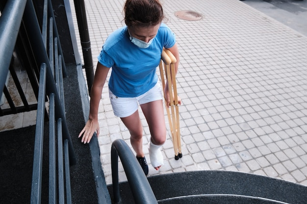 A woman with a broken leg climbs the stairs.