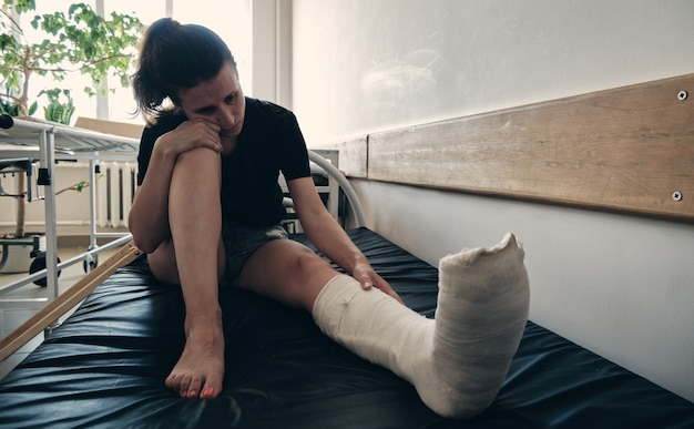 A woman with a broken leg sits on a hospital couch and regrets  rehabilitation after a fracture
